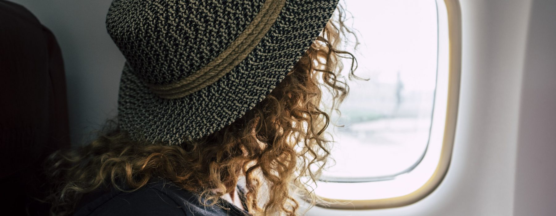 Woman travel on aircraft flight - fly for business or holiday vacation people inside airplane looking outside from the window - concept of transport and freedom